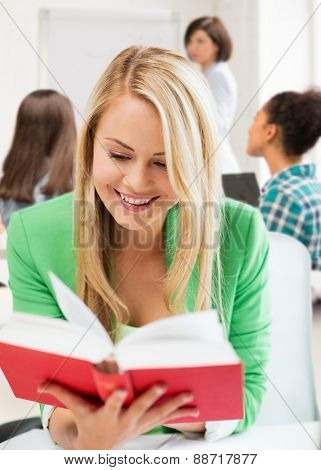 education concept - smiling student girl reading book at school