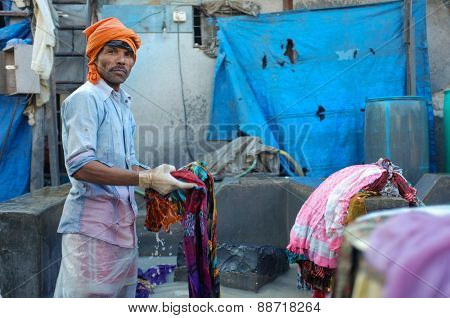 MUMBAI, INDIA - 10 JANUARY 2015: Indian worker washing a sari in Dhobi ghat.