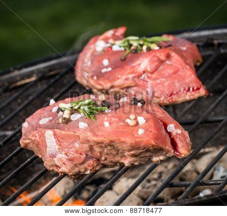 Raw beef steaks on grill
