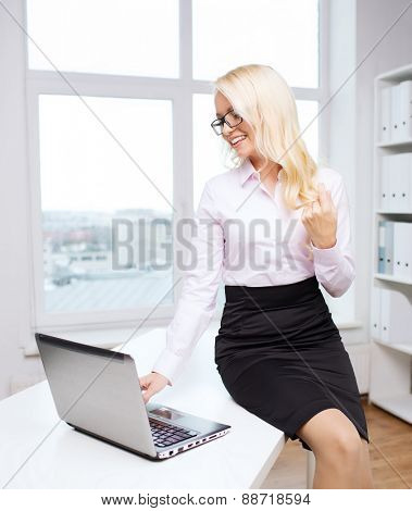education, business, flirting and technology concept - smiling businesswoman or secretary with laptop computer sitting on table in office