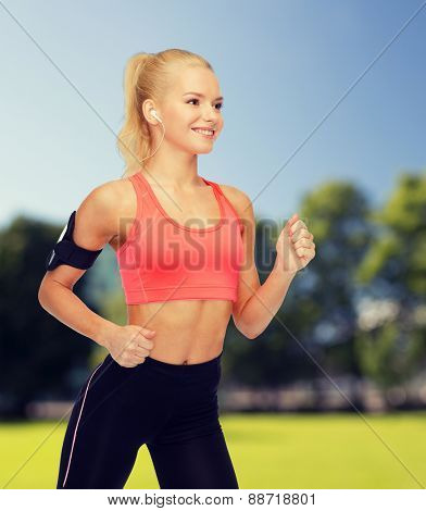 sport, exercise, technology, internet and healthcare - smiling sporty woman running and listening to music from smartphone
