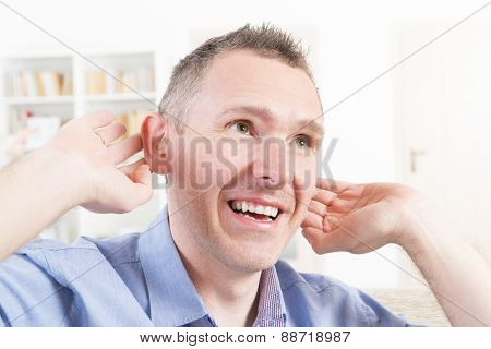 Man wearing deaf aid in ear attempting to hear something