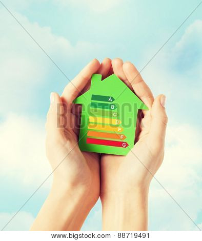 energy saving, real estate and family home concept - closeup of female hands holding green paper house with energy efficiency rating
