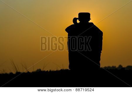 Silhouette shot of Army water canteen on sunset background.