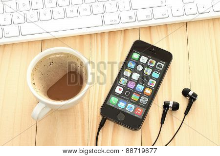 KIEV UKRAINE - APRIL 15 2015:iPhone 5s Space Gray with coffee and keyboard on wooden background.