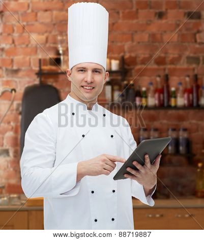 cooking, profession and people concept - happy male chef cook holding tablet pc computer over kitchen background