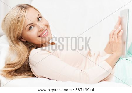 smiling woman lying on the couch with tablet pc
