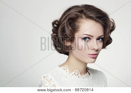 Portrait of young beautiful woman with curly prom hairdo in vintage style