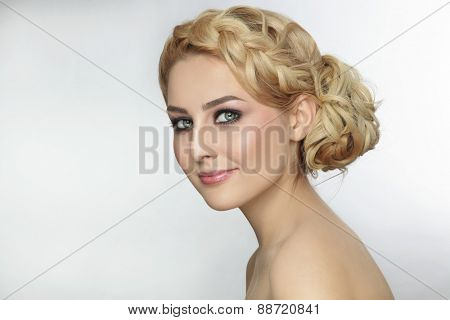 Portrait of young beautiful blonde woman with stylish prom hairdo