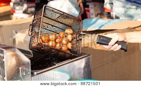 cooking, asian kitchen and food concept - close up of cook frying meatballs in oil at street market