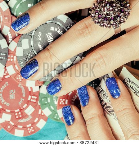 hands of young caucasian woman with blue manicure at casino tabl