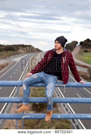 Cool handsome man at the top of a bridge over a highway