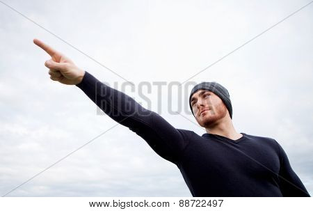 Cool handsome guy with beard at outside pointing something
