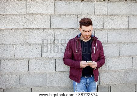 Casual cool young man with beard looking the mobile