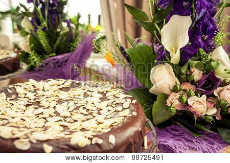 Luxury cake with almonds among flowers. Soft focus on pie's leading edge
