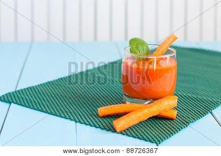 Healthy homemade carrot juice in glass and fresh carrots on light wooden background.