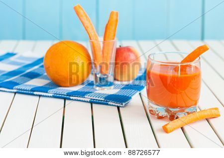 Healthy homemade carrot juice in glass and fresh carrot, apple, orange, lemon on light wooden backgr