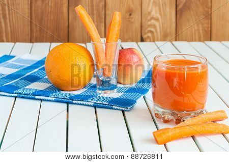 Healthy homemade carrot juice in glass and fresh carrot, apple, orange on light wooden background.