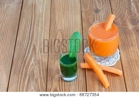 Healthy homemade carrot juice in glass and fresh carrot, spinach on light wooden background.