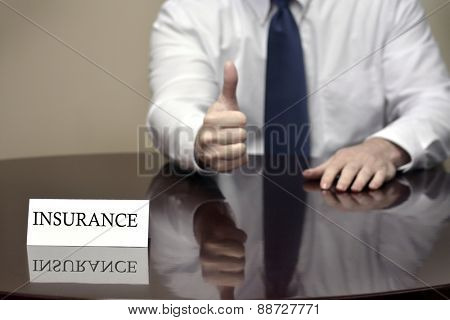 Insurance agent sitting at desk holding hand with thumbs up sign for good coverage