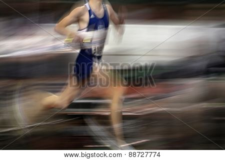 Runner running a race around a track with  lines holding baton relay