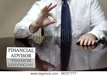 Financial advisor sitting at desk holding OK sign on hand to show good plan