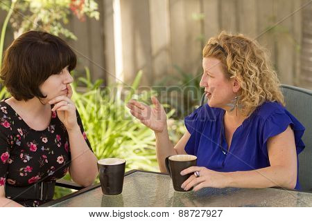 Two Women Sharing And Chatting Over Coffee.