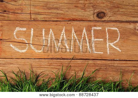 Summer written in chalk on a wooden fence.