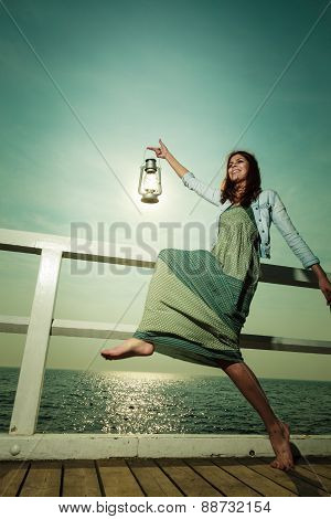 Young Woman On Pier With Oil Kerosene Lamp.