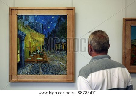 OTTERLO, NETHERLANDS - AUGUST 8, 2012: Visitor looks at the painting Cafe Terrace at Night (1888) by Vincent van Gogh in the Kroller Muller Museum in Otterlo, Netherlands.