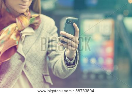 Young Woman with mobile phone, background is blured city