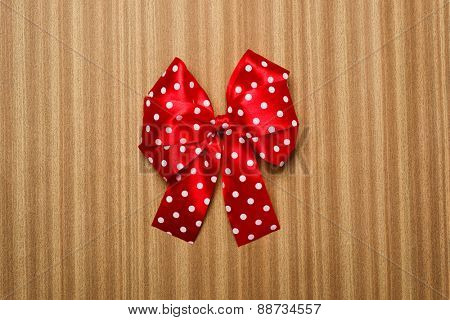 red bow on wooden background