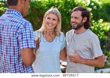 friends chatting outdoors at garden party gathering with cocktail wine drinks