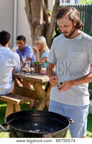 young man preparing to start fire for friends outdoor barbecue garden party