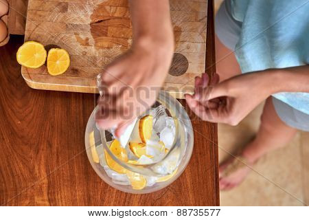 Woman putting ice and lemon in jug for a refreshing drink in kitchen