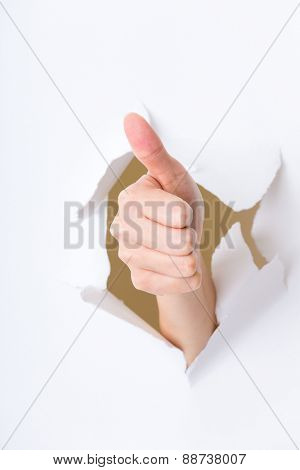 Thumb up hand gesture break through the paper wall