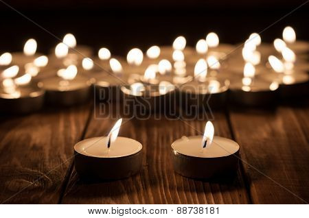 Couple of candle and blurry candles on old wooden background