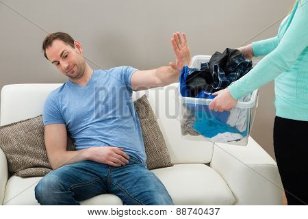 Man Ignoring Dirty Clothes Hold By A Woman