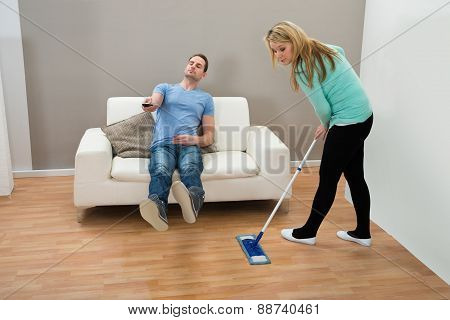 Woman Cleaning Floor While Man On Sofa