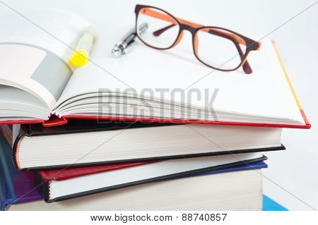 Books Stack With Open Book And Glasses