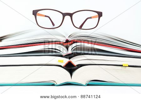 Glasses On Stack Of Open Books
