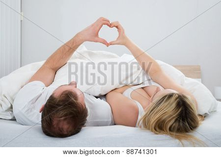 Couple Forming Heart Shape With Hand