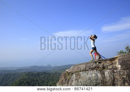 cheering young woman hiker yelling at mountain peak