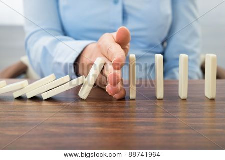 Businesswoman Stopping The Effect Of Domino