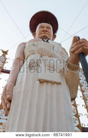 Buddhist Monk In White Robe Statue With Walking Stick