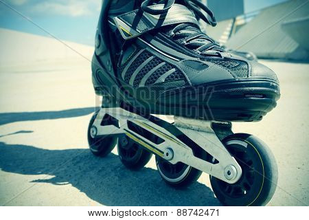 closeup of the feet of a young man roller skating with inline skates, with a slight vignette added