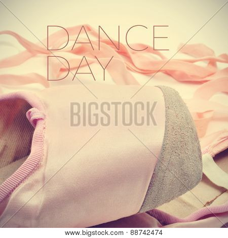 closeup of a pair of classic pink pointe shoes and the text dance day, with a retro effect