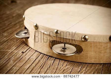 closeup of a tambourine on a rustic wooden table, heavy processing for retro bleached look