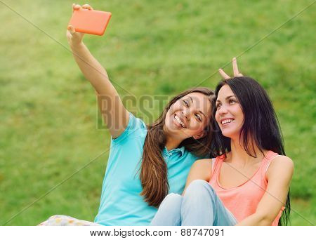 Two Women Friends Having Fun And Taking Pictures Of Themselves With Smart Phone On Picnic At The Par