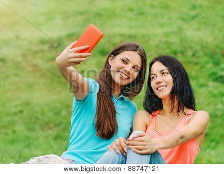 Two Women Friends Smiling And Taking Pictures Of Themselves With Smart Phone On Picnic At The Park